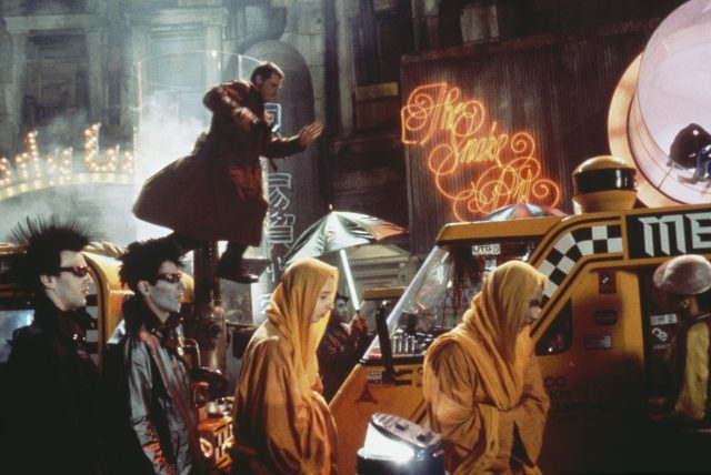 Blade Runner, Deckard (Harrison Ford) pursues Replicant, Zhora (Joanna Cassidy) through the crowded streets of a hellishly dystopian future Los Angeles