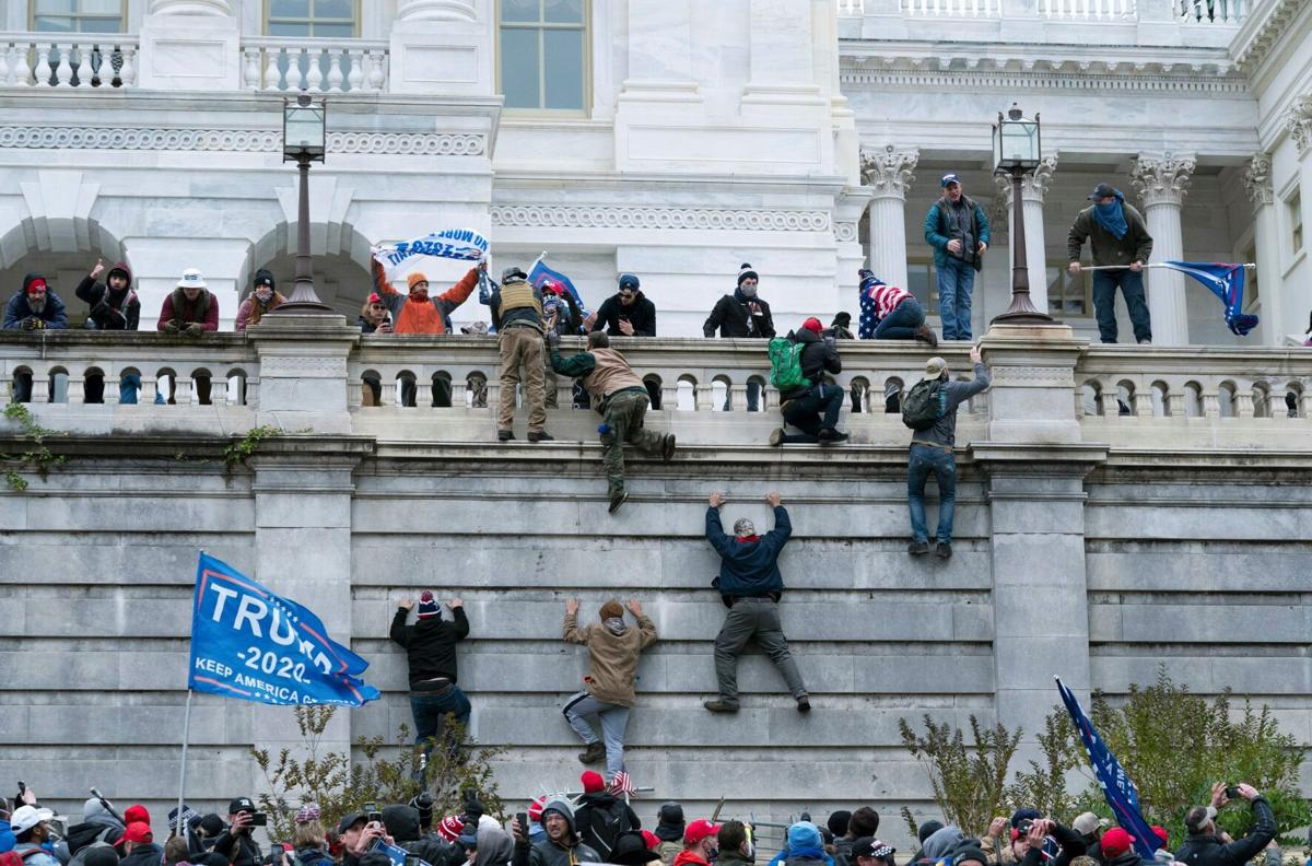 Trump supporters climb the west wall of the Capitol.