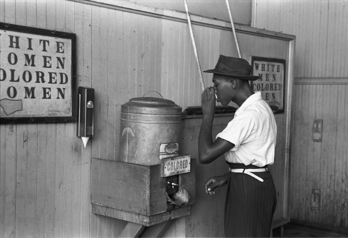 "African-American man drinking from a ""Colored"" water cooler in streetcar terminal, Oklahoma City, mid-20th century"