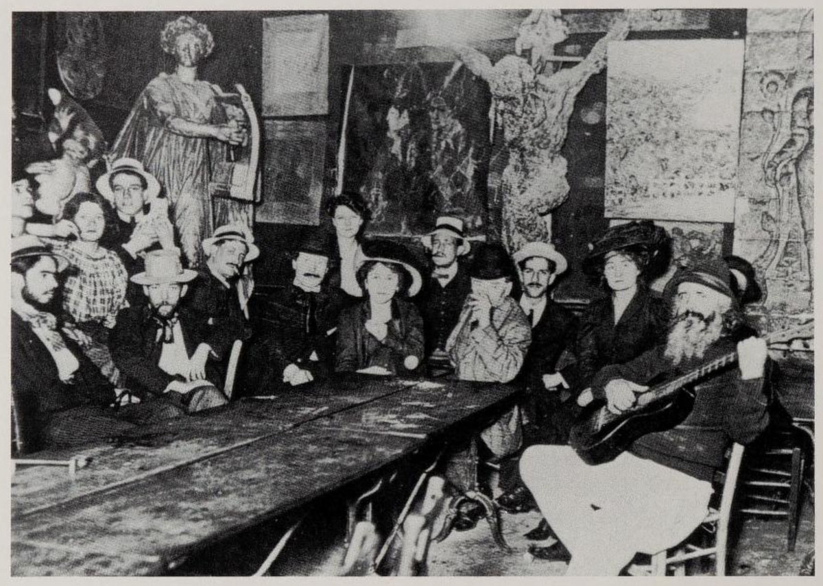 A gathering at the Lapin Agile in Montmartre. The cafe's proprietor, Frédé, is seated far right, playing his guitar. Picasso's painting Au Lapin Agile hangs on the back wall.